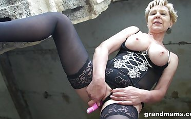 Sexy old woman in stockings coupled with corset is toying pussy in an abandoned building